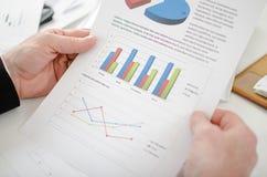 Крупный план бизнесмена смотря диаграмму Стоковые Изображения