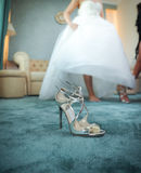 Крупный план ботинка свадьбы серебряный с невестой в предпосылке Ботинок высоких пяток bridal на ковре Невеста получая готовый на Стоковое фото RF