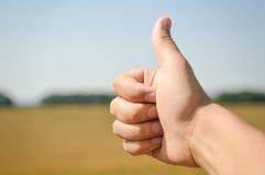 Крупный план большого пальца руки вверх по руке на предпосылке солнечного дня outdoors, поднимающем вверх изображения близкое Стоковая Фотография RF