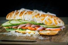 Крупный план бургера на деревянной доске с темной предпосылкой Стоковое Изображение RF
