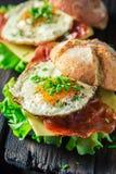 Крупный план бургера с салатом, беконом и яичками Стоковое фото RF