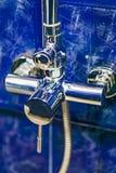 Крупный план ванной комнаты смесителя, плиток терракоты предпосылки голубых Стоковая Фотография RF