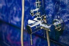 Крупный план ванной комнаты смесителя, плиток терракоты предпосылки голубых Стоковое Фото