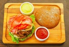 Крупный план вверх очень вкусного гамбургера с говядиной, луком, томатом, салатом и сыром на деревянной доске, над взглядом Стоковое фото RF