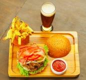 Крупный план вверх очень вкусного гамбургера с говядиной, луком, томатом, салатом и сыром на деревянной доске, над взглядом Стоковая Фотография