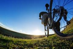 Крупный план велосипедиста на горном велосипеде спорта дорога пущи сельской местности, котор нужно переместить Стоковые Фото