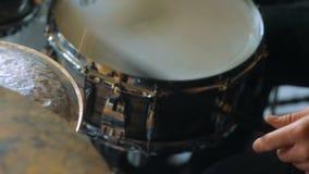 Крупный план взгляда со стороны человека играя барабанчики в студии сток-видео