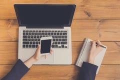 Крупный план взгляд сверху женщины используя телефон на рабочем месте Стоковое Изображение