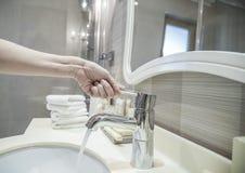 Крупный план водопроводного крана отверстия руки в ванной комнате Стоковое фото RF