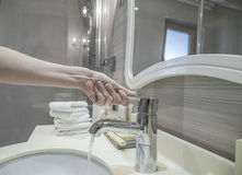 Крупный план водопроводного крана отверстия руки в ванной комнате Стоковые Изображения RF