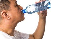 Крупный план воды человека выпивая освежая холодной от бутылки Стоковые Изображения