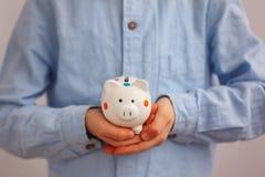 Крупный план вручает ребенк держа копилку или денежный ящик Стоковые Фото
