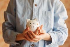 Крупный план вручает ребенк держа копилку или денежный ящик Стоковые Изображения