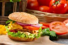 Крупный план гамбургера с цыпленком, томатом и овощами Стоковые Фото