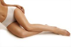 Крупный план девушки лежа на поле показывая красивые ноги Стоковое Фото