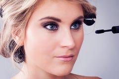 Крупный план девушки прикладывая состав глаза. стоковое изображение rf