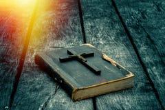 Крупный план деревянного христианского креста на библии на старой таблице стоковое фото