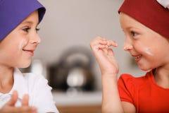 Крупный план детей делая торты и усмехаться Стоковая Фотография RF
