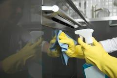 Крупный план женских рук в перчатках очищая печь, держа брызг Стоковая Фотография