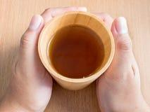 Крупный план женских рук держа деревянную чашку органического чая жасмина Стоковая Фотография RF