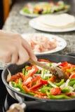 Крупный план женщины варя овощи и цыпленка в лотке Стоковые Изображения
