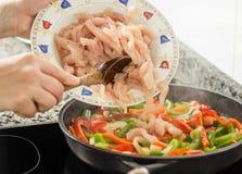 Крупный план женщины варя овощи и цыпленка в лотке Стоковое Изображение RF