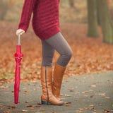 Крупный план женщины в коричневых ботинках с зонтиком Стоковые Изображения RF
