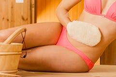 Крупный план женщины в сауне с exfoliating перчаткой Стоковые Изображения