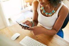 Крупный план женщины используя сотовый телефон в офисе Стоковые Фото