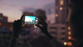 Крупный план женщины принимая фото взгляда городского пейзажа с smartphone в террасе на крыше бара на ночу видеоматериал