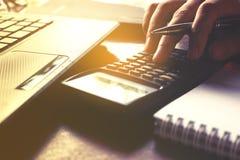 Крупный план женщины руки используя калькулятор и высчитывает о цене Стоковое Изображение