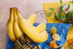 Крупный план желтых ярких бананов, зеленых свежих листьев мяты, физалиса на синей салфетке на красочной предпосылке Стоковая Фотография RF