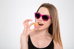 Крупный план забавных macaroons дегустации молодой женщины Стоковые Фотографии RF