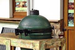 Крупный план зеленого керамического гриля BBQ установленного в таблице Стоковые Фотографии RF