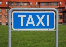 Крупный план знака такси с предпосылкой здания и травы Стоковое Изображение
