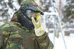 Крупный план игрока пейнтбола в маске при выплеск краски показывая pe Стоковая Фотография