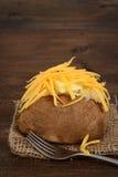 Крупный план испеченной картошки с маслом и сыром Стоковые Изображения