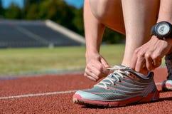 Крупный план идущих ботинок, женский спортсмен бегуна связывая шнурки для тренировки и jogging на следе стадиона, спорте и фитнес Стоковые Фотографии RF