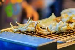 Крупный план кальмара приготовления на гриле, экзотическая еда улицы на метке ночи Стоковые Изображения RF