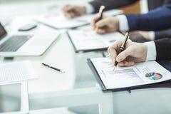 Крупный план команды дела работает с финансовыми план-графиками в рабочем месте в офисе Стоковая Фотография