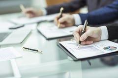 Крупный план команды дела работает с финансовыми план-графиками в рабочем месте в офисе Стоковые Фотографии RF