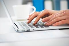 Крупный план коммерсантки печатая на портативном компьютере Стоковые Фото
