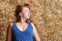 Крупный план красивой девушки при длинные светлые волосы лежа на сене Стоковое Фото