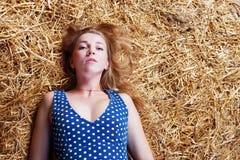 Крупный план красивой девушки при длинные светлые волосы лежа на сене Стоковые Изображения