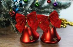 Крупный план 2 красивый красный сияющий колоколов на предпосылке рождественской елки и сусали на деревянном поле Стоковое Изображение