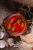 Крупный план красного пикантного papper chili в стеклянном опарнике, хворостинах розмаринового масла и раковинах яичек триперсток Стоковое Фото