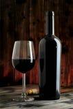 Крупный план красных бокала и бутылки, на античном деревянном столе Стоковое Фото