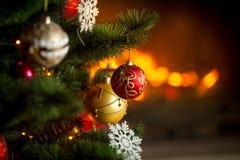 Крупный план красных и золотых безделушек вися на рождественской елке на b Стоковые Фото