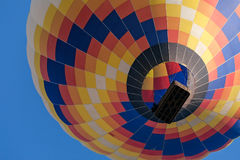 Крупный план красочного использующего горячего воздух воздушного шара в полете увиденном снизу Стоковое Изображение RF