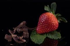 Крупный план клубники с листьями и шоколадом мяты на черном ба Стоковая Фотография